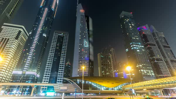 Downtown Dubai towers night timelapse hyperlapse. View of Sheikh Zayed road with tall skyscrapers. Traffic on the road and metro line. Blinking lights and trails Royalty-free stock video