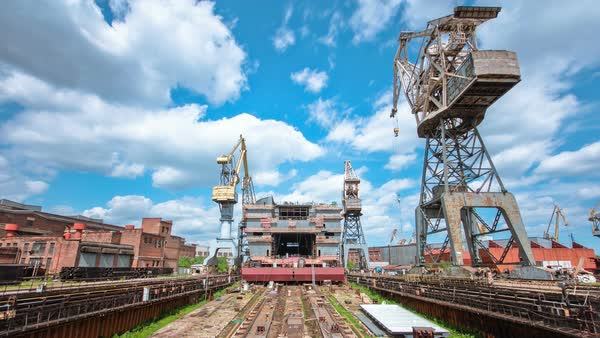 Construction of the ship in shipyard timelapse with cranes. Blue cloudy sky Royalty-free stock video