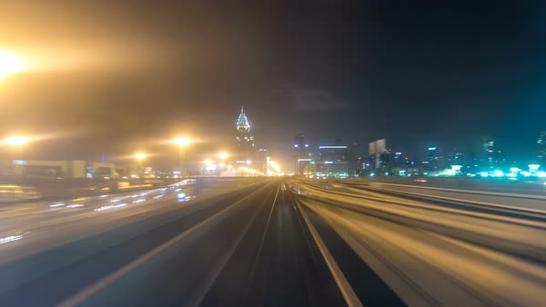 Front cabin POV view from modern driver-less metro train rush forward, along night Dubai, smooth timelapse. Overground railway, dark low rise buildings around, bright road lights at night. Motion from downtown Royalty-free stock video