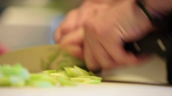 Person cutting celery. close-up of hands and knife cutting celery. Royalty-free stock video