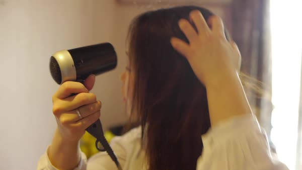 Close-up tracking shot of woman using a hair dryer in Korea Royalty-free stock video