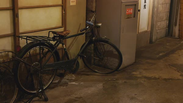 Hand-held shot of an old bicycle parked on a street in Osaka Royalty-free stock video