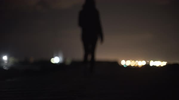 Out of focus shot of a woman walking away from camera on a shore Royalty-free stock video