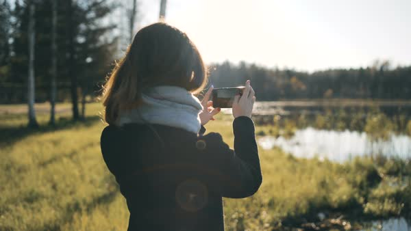Young woman takes a photo with her phone of the lake and then walks away Royalty-free stock video