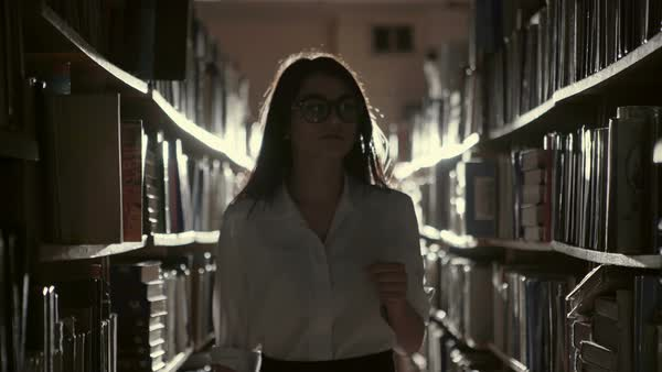 Woman standing in an aisle in a library between rows of books using torchlight during a power failure backlit by a beam of light with lens flare Royalty-free stock video