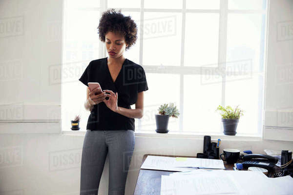 Young black businesswoman using phone by window in an office Royalty-free stock photo