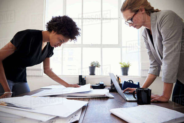 Two women work at opposite sides of an office desk, close up Royalty-free stock photo