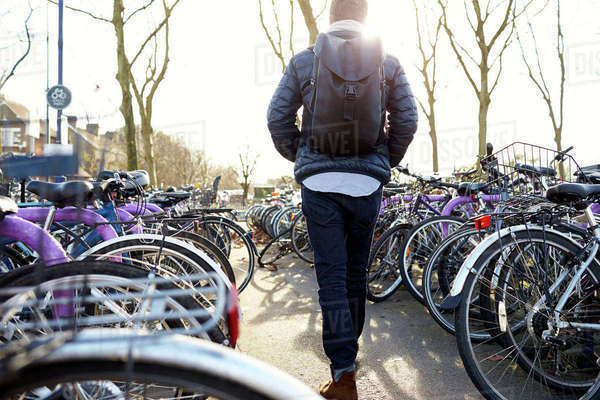 Rear view of man leaving bike in cycle park at rail station Royalty-free stock photo