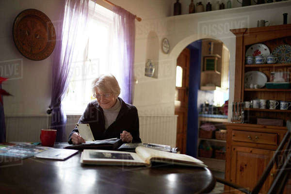 Senior woman looking through photo album at home Royalty-free stock photo