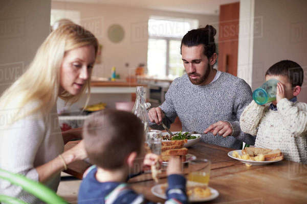 Family sitting at kitchen table and eating meal together Royalty-free stock photo