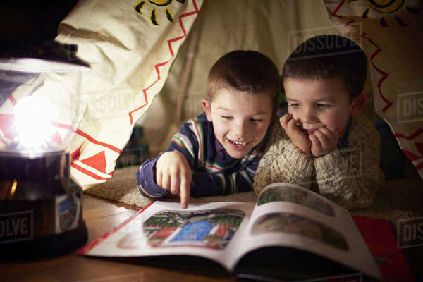 Two young boys reading inside tent set up indoors Royalty-free stock photo