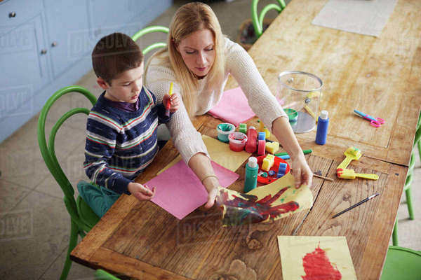 Mother and son sitting at kitchen table and painting picture Royalty-free stock photo