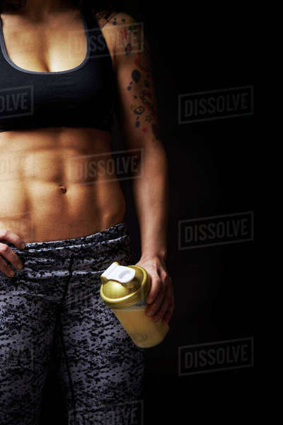 Mid-section crop of muscular young woman holding drink cup Royalty-free stock photo