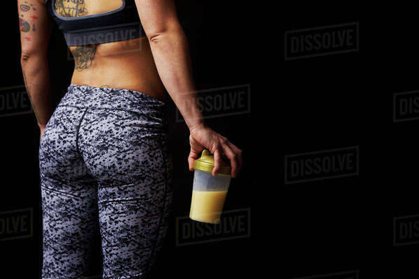 Mid-section of muscular young woman holding drink, back view Royalty-free stock photo