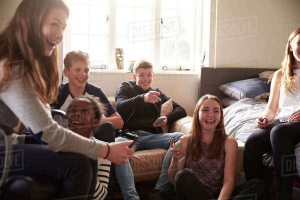 Group of teenagers playing video game in bedroom Royalty-free stock photo