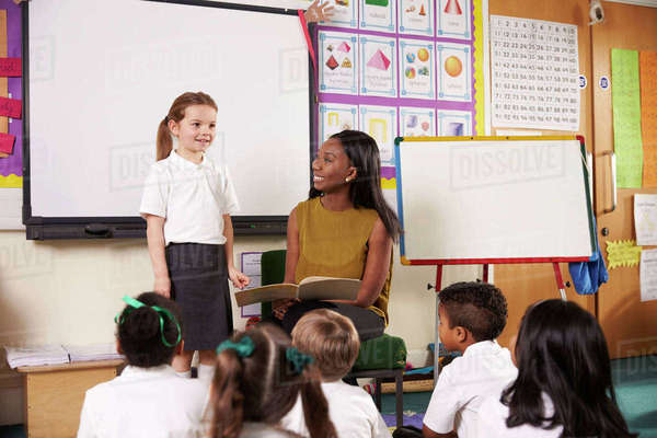 Female elementary pupil reading in front of class Royalty-free stock photo