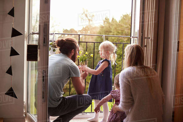 Family at home looking at plants on balcony Royalty-free stock photo