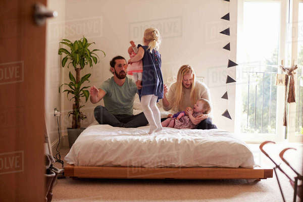 Parents playing game with daughters in bedroom Royalty-free stock photo