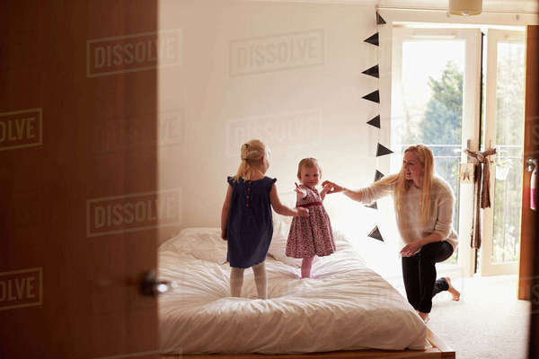 Mother playing game with daughters in bedroom Royalty-free stock photo