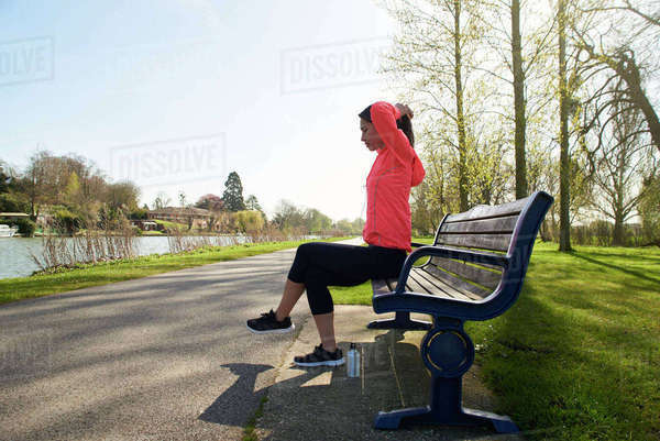 Young Woman Sitting On Park Bench Stretching Before Exercise Royalty-free stock photo