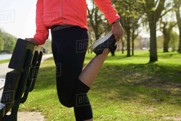 Young Woman Stretching On Park Bench Before Exercise Royalty-free stock photo