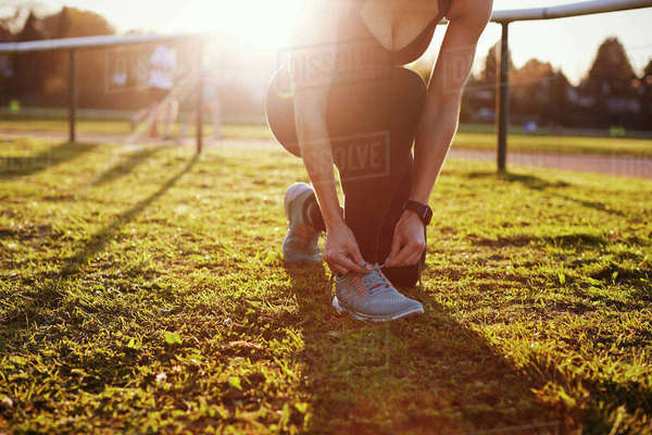 Close Up Of Woman Lacing Trainers Before Outdoor Exercise Royalty-free stock photo