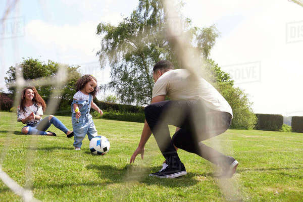 Parents squat to play football with their young daughter Royalty-free stock photo