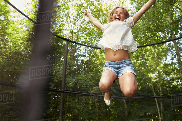 Girl having fun jumping on trampoline in a garden Royalty-free stock photo