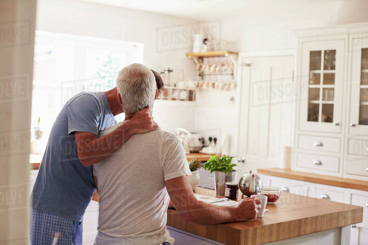 Male Couple Kiss In Their Kitchen In The Morning Back View Stock Photo Dissolve
