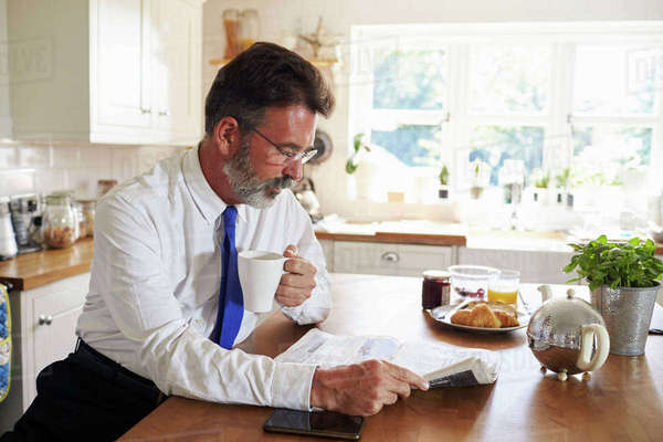 Man in tie holding cup reads newspaper in kitchen, close up Royalty-free stock photo