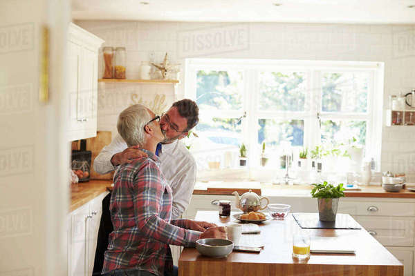 Male couple kissing before one leaves for work, side view Royalty-free stock photo