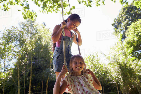 Two girls on a tyre swing, one looking to camera, close up Royalty-free stock photo