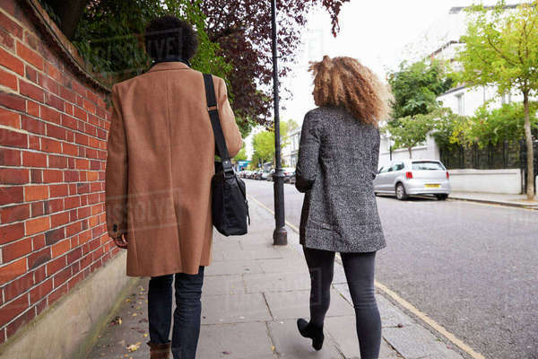 Rear View Of Stylish Couple Walking Along Street In City Royalty-free stock photo