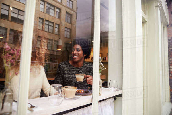 View Through Window Of Couple Enjoying Drink In Coffee Shop Royalty-free stock photo