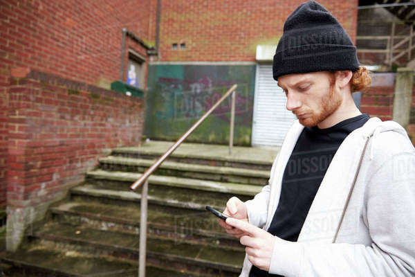 Skater using smartphone in an urban setting, waist up Royalty-free stock photo