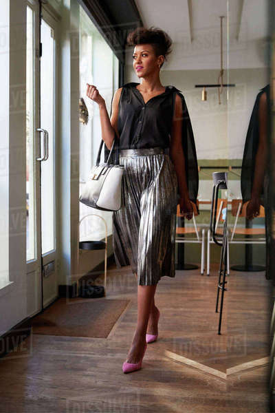 Fashionable young woman with handbag walking in a cafe Royalty-free stock photo