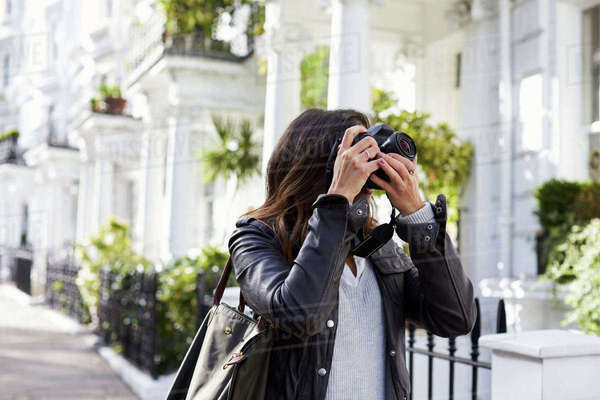 Young woman taking photo in a residential city street Royalty-free stock photo