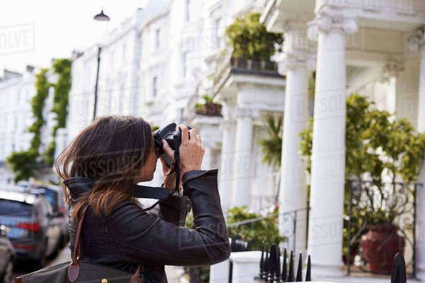 Young woman taking photo in a residential city street, side view Royalty-free stock photo