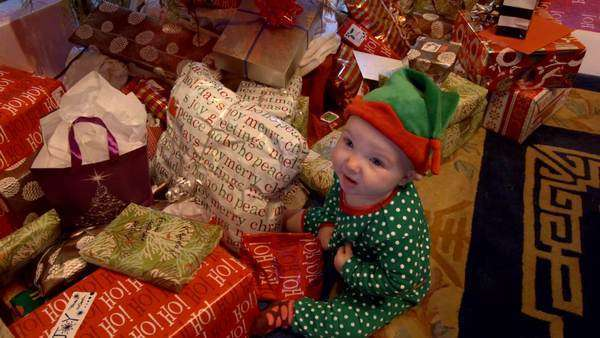 Hand-held shot of a baby sitting next to Christmas presents Rights-managed stock video
