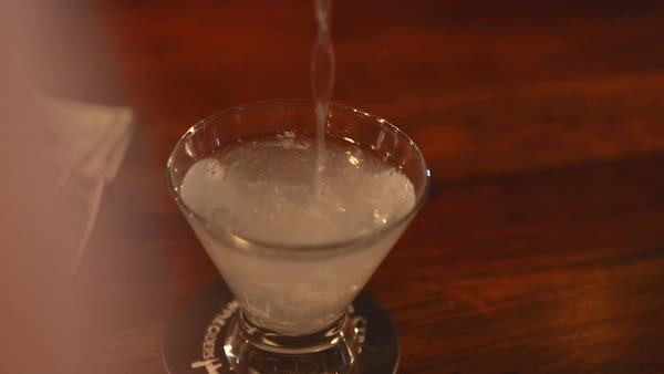 Hand-held shot of a bartender pouring martini Rights-managed stock video