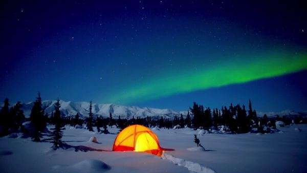 Static shot of a tent with northern lights in background Rights-managed stock video