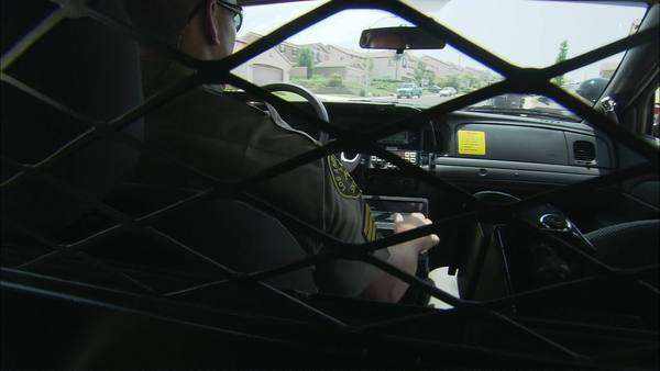 Hand-held shot of a deputy officer having a radio call in patrol car Rights-managed stock video