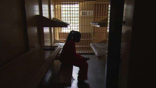 Static shot of a female prisoner sitting in her cell Rights-managed stock video