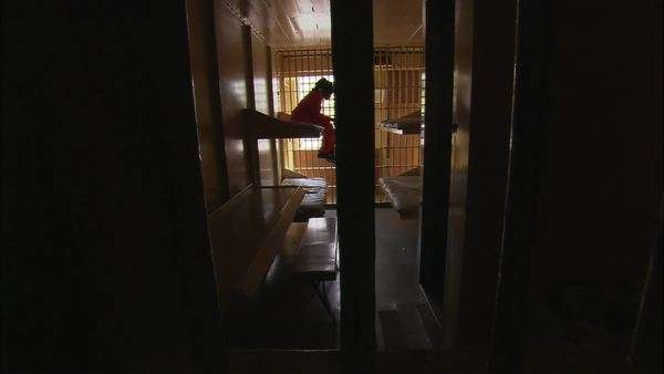 Static shot of a female prisoner sitting in her cell while doors are closing Rights-managed stock video