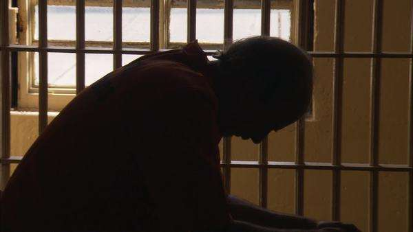 Zooming out shot of a prisoner sitting in his cell Rights-managed stock video