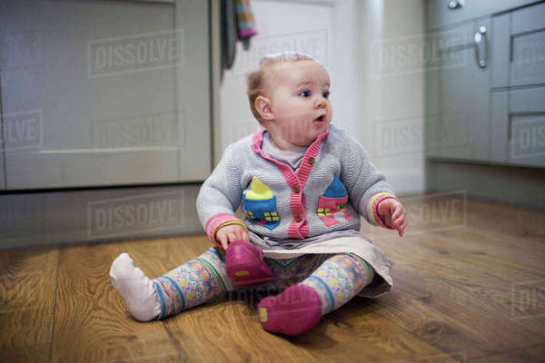 Baby girl sitting on floor with shoes at home Royalty-free stock photo