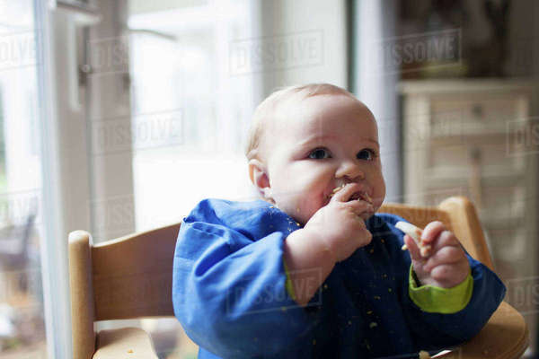 Baby girl sitting in high chair at meal time Royalty-free stock photo