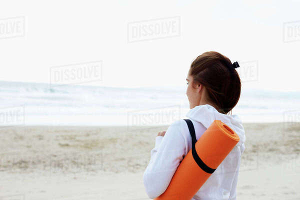 Woman carrying mat goes onto beach for yoga exercise Royalty-free stock photo