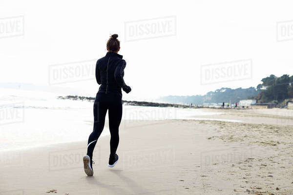 Young woman exercising by running on beach Royalty-free stock photo