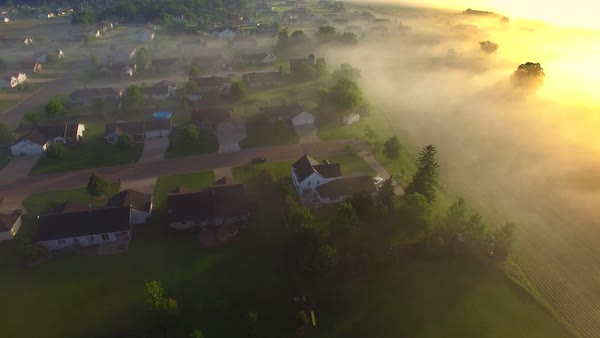 Beautiful neighborhoods, homes, suburbs, under spectacular foggy sunrise, aerial view. Royalty-free stock video